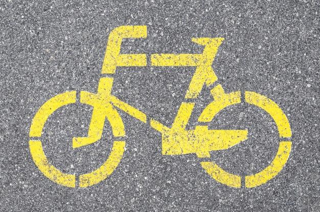 アスファルトに黄色のペンキが付いた自転車道の標識。