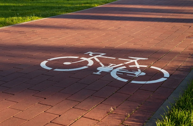 Bicycle path with the bike icon on pavement in the city public park.