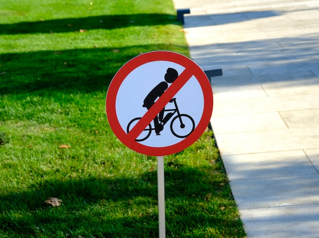 The bicycle prohibited sign on the wood pole at the entrance of the park.