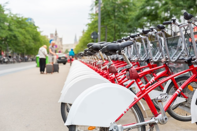Bicycle rental, europe, bike rent parking. urban eco transport, human powered vehicle, row of red cycles, nobody