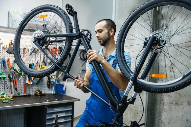 Ремонт велосипедов в мастерской, человек проверяет механизмы