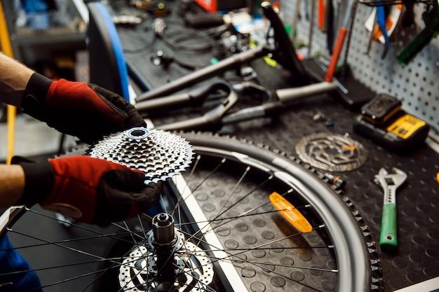 Ремонт велосипедов в мастерской, мужчина устанавливает звездную кассету