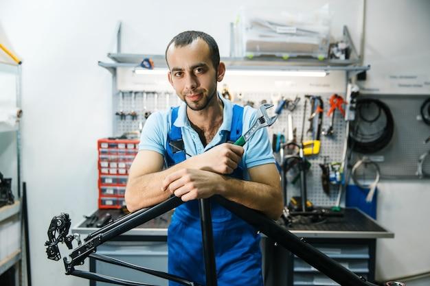 Ремонт велосипедов в мастерской, мужчина позирует у рамы
