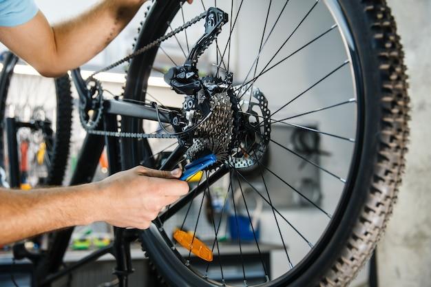 Ремонт велосипедов в мастерской, мужчина настраивает кассету крупным планом