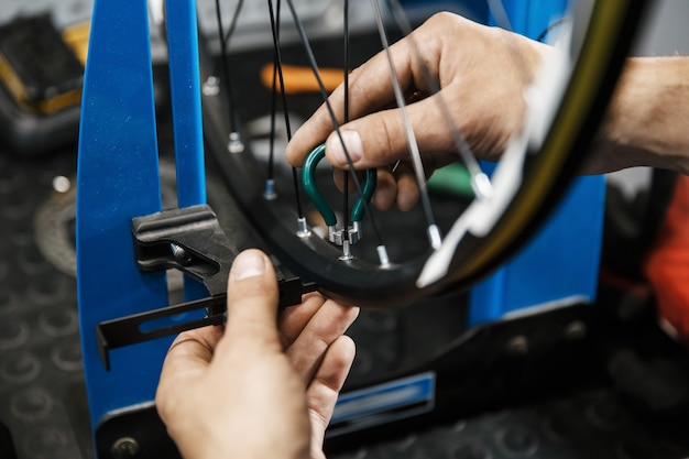 Ремонт велосипедов в мастерской, человек затягивает спицы на колесе