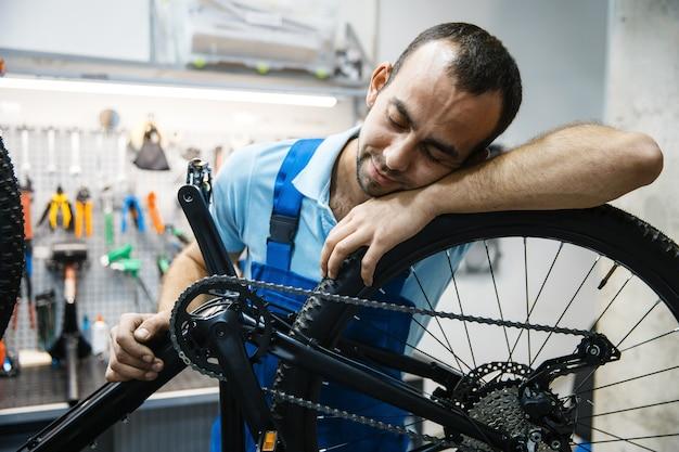 Ремонт велосипедов в мастерской, усталый ремонтник спит на рабочем месте