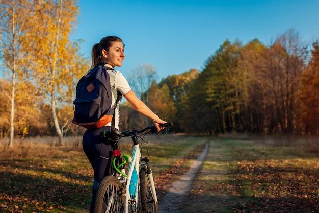秋の公園で自転車に乗る、郊外で自転車に乗った後休む若い女性旅行者、