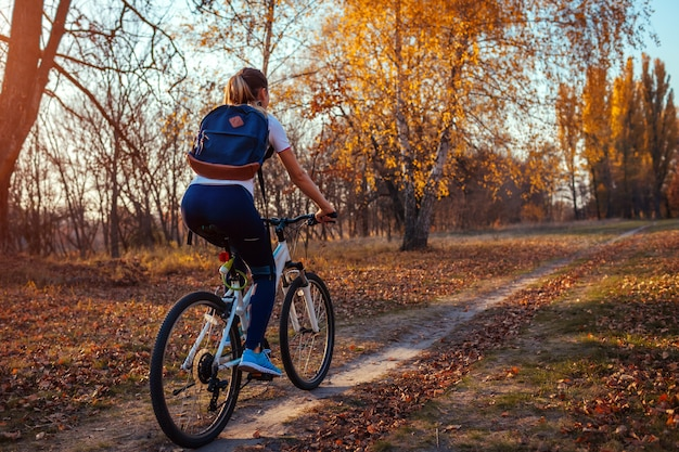 Bicycle ride workout in autumn park, young woman biker riding a bike in fall forest,