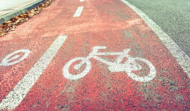보도 경계에 단풍이 있는 거리 자전거 도로의 자전거 도로 기호