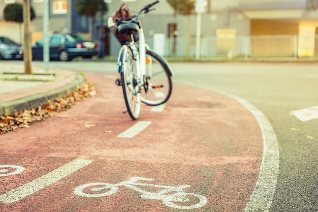 Bicycle road symbol over a street bike lane in autumn with white bicycle on the background