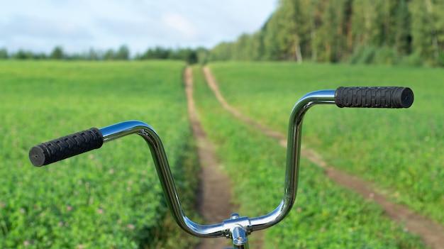 夏の背景の遠くに伸びる田舎道のある前景の自転車の舵
