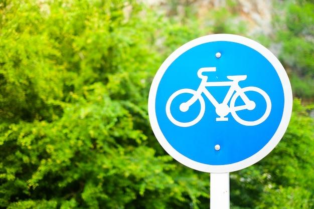 自転車は緑の自然に分離された青い金属サイクルにサインオンします。