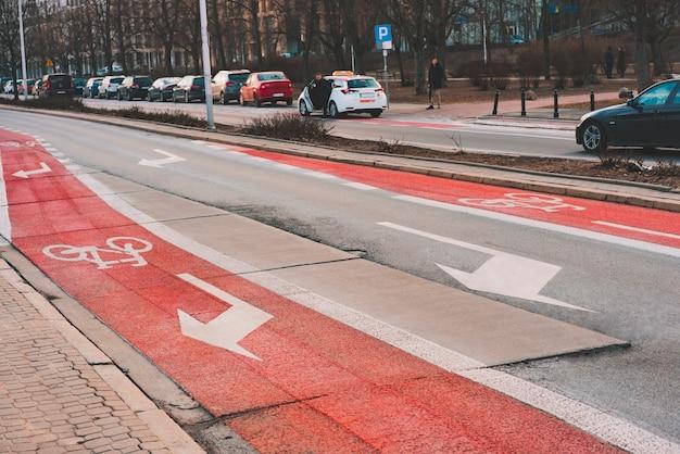 Знак велосипеда нарисовал на поверхности дороги красная велосипедная дорожка в городе. часть проезжей части предназначена только для велосипедистов. указатели поворота. безопасность. безопасность. велосипедная дорожка. асфальтированная дорога