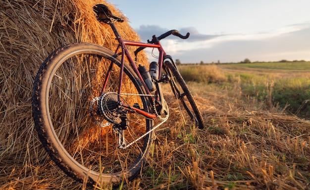 自転車は日没時に干し草の山のそばの畑に立っています。