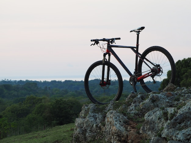 A bicycle stands on top of a hill at dusk.