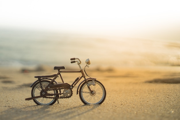 Bicycle transport toy on sand sea beach in the evening sunset sky