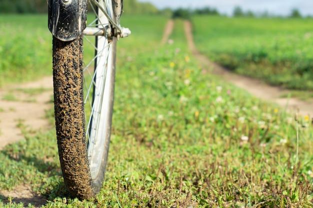 夏の背景の遠くに伸びる田舎道と前景の自転車の車輪