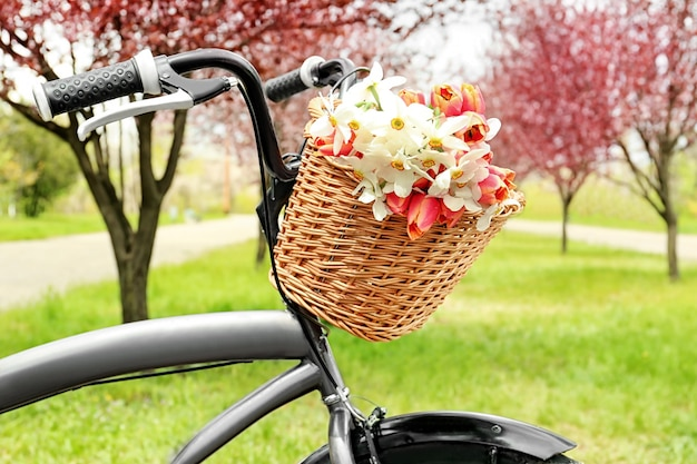 Bicycle with basket of beautiful flowers on blurred