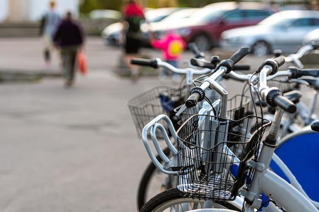 焦点がぼけた通りの壁の駐車場に貸し自転車が立っている