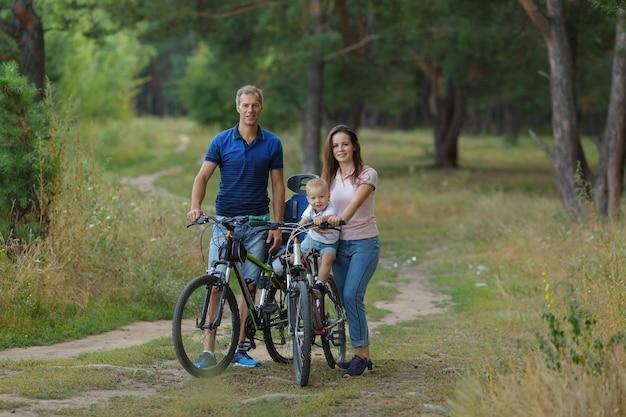Семья велосипедистов, отдых в сосновом лесу, счастливые родители. пара с сыном ходит на велосипедах в парке, езда на велосипеде. copyspace