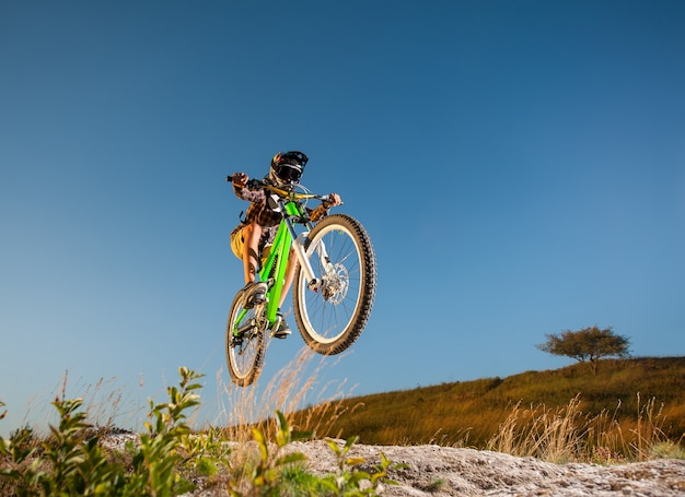 Bicyclist jumping on a mountain bike on the mountain against blue sky