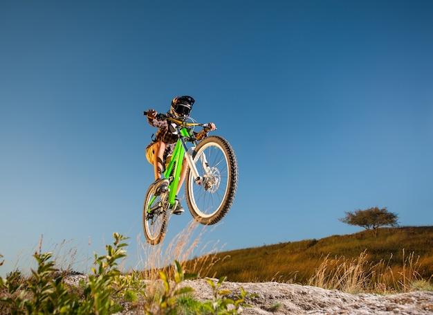Велосипедист, прыжки на горном велосипеде на горе против голубого неба