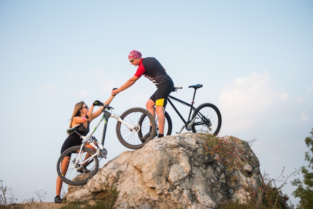 Bicyclist pulls the hand woman with a mountain bike into steep hill against evening blue sky