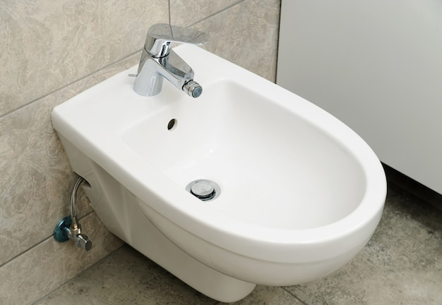 Bidet with water faucet fixed on the wall.