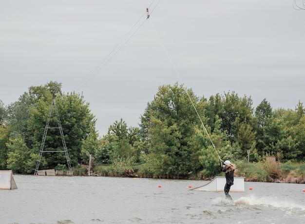 Белява, польша. 06.03.2020 wawa wake. молодая спортсменка скользит на водных лыжах по волнам озера. девушка катается на вейкборде