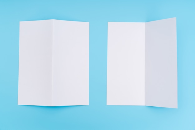 Bifold white template paper on blue background .
