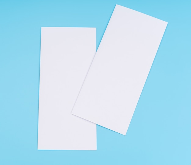 Бифолд белый шаблон бумаги на синем фоне.