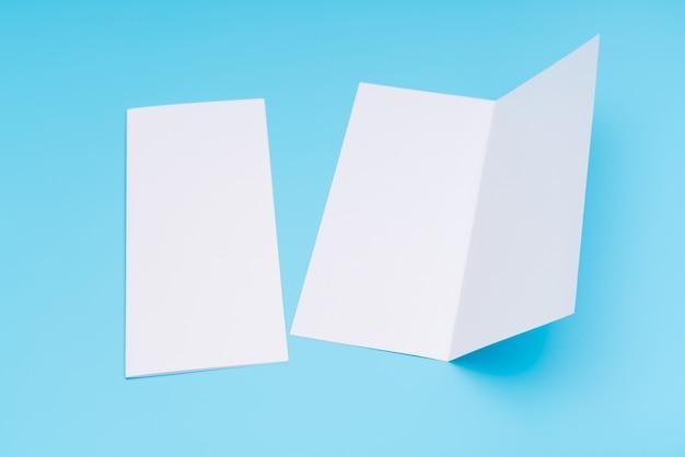 青い背景の2倍の白いテンプレート紙。