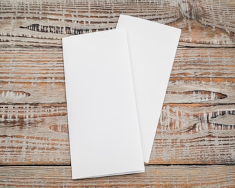 Bifold white template paper on wood texture .