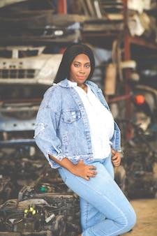 Моделирование большой афро-американской женщины. автозапчасти старой машины на складах. автомеханик автосервис, ремонт и концепция технического обслуживания. б / у автозапчасти