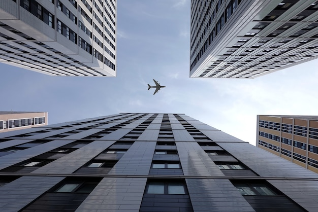 Big airplane flying high above modern city skyscraper buildings with many windows in business cluster view bottom up on bright sunny day