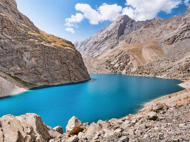 ロッキー山脈の背景に日差しの中で青緑色の水と大きなアロ山湖。中央アジア、タジキスタン、ファン山脈