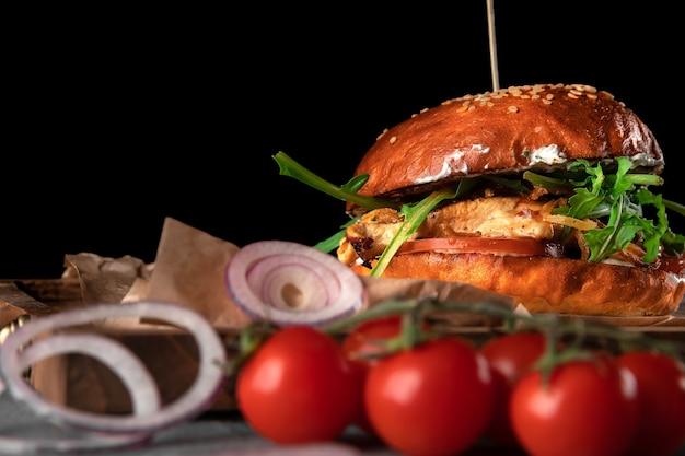 黒の背景に大きなアメリカのハンバーガー。木製トレイにチーズ、トマト、チキン、ルッコラのコートレット、コピースペース、クローズアップ