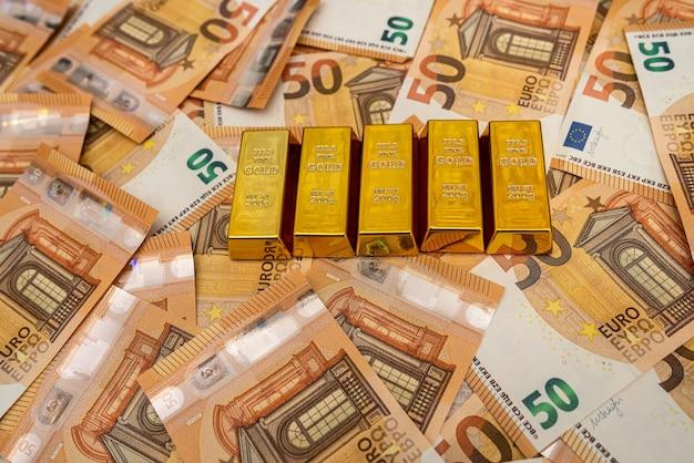 큰 금액의 50 유로 돈 지폐와 금괴 저축 개념