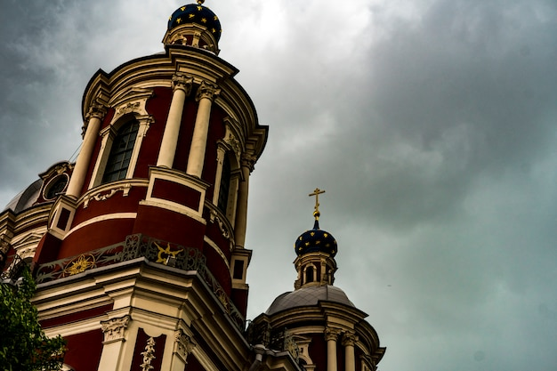 Big ancient church against the dark cloudy sky during severe storm
