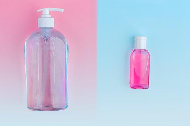 Большие и маленькие бутылки с антисептическим дезинфицирующим гелем для мытья рук на синем и розовом фоне. алкоголь гель как профилактика коронавируса. концепция профилактики вирусных заболеваний.