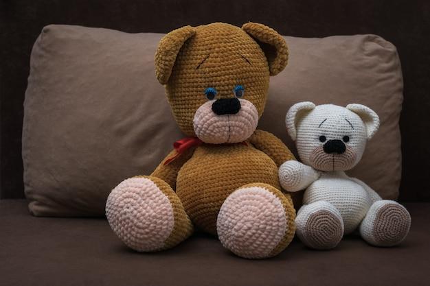 ソファの上の抱擁に座っている大小のニットクマ。美しいニットのおもちゃ。