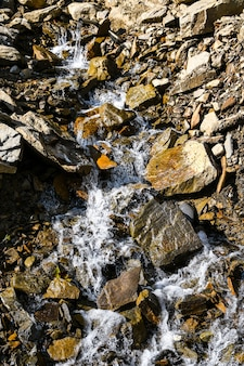 Большие и маленькие камни у ручья. горы. фактура камня. задний план. вода падает на камни. красота в природе