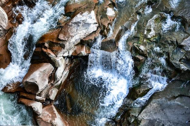 개울 근처의 크고 작은 돌. 산. 돌의 질감입니다. 배경. 물이 바위에 떨어집니다. 자연의 아름다움