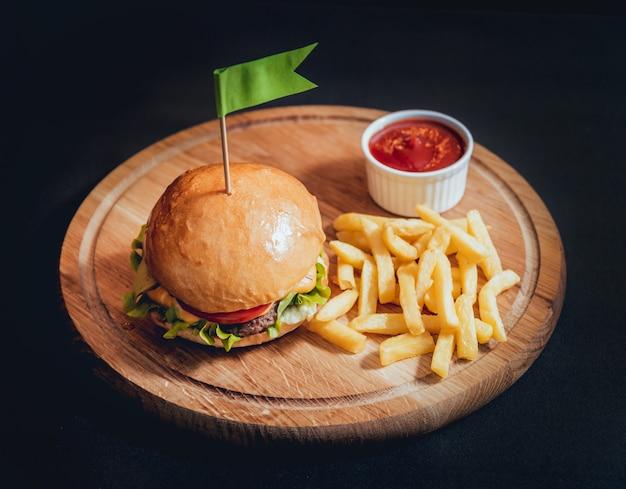 Большой и вкусный бургер с огнями на деревянный стол.