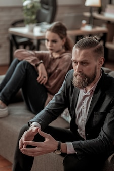 Big argument. top view of bearded father and daughter sitting on sofa after big argument