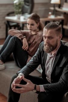 大きな議論。大きな口論の後、ソファに座っているひげを生やした父と娘のトップビュー