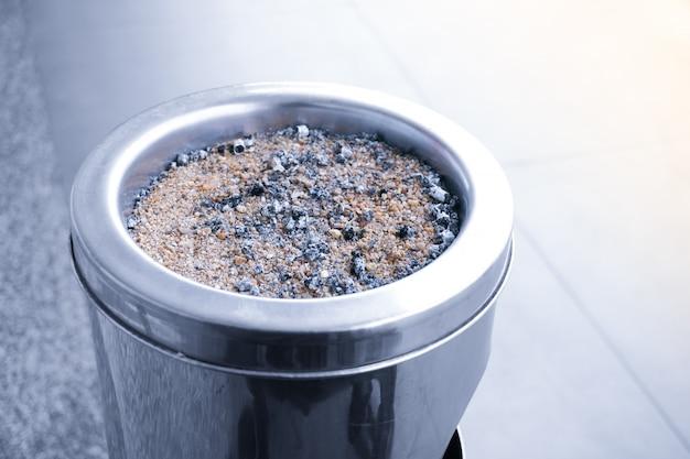 喫煙者が屋外の制限された喫煙エリアでのみ喫煙できる多くのタバコのある大きな灰皿。