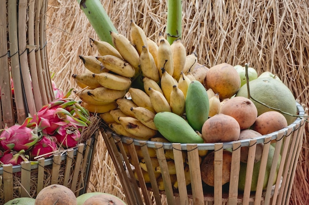 Big basket with asian fresh fruits on bamboo bench.