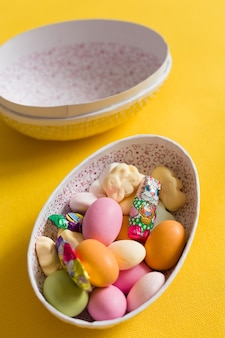 사탕과 초콜릿 스칸디나비아 전통이 있는 큰 비스터 달걀 상자는 노란색 배경에 닫혀 있습니다