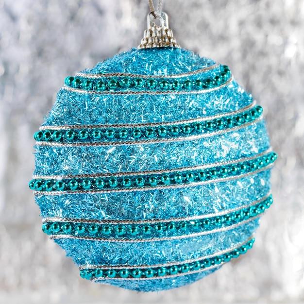 明るいぼやけた背景に大きな美しい青いボール。お祝いのグリーティングカード。新年、クリスマスの背景。